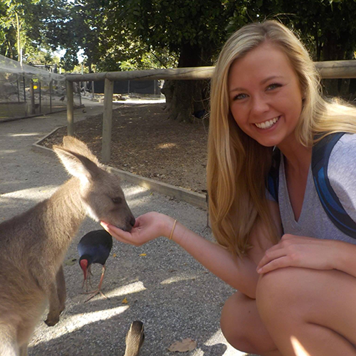 Shannon Corcoran pets a Kangaroo in New Zealand